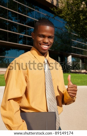 Happy young African-American businessman smiling and giving a thumbs-up sign