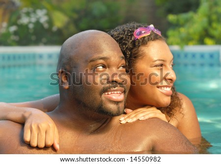Happy young African American couple relaxing in the pool - stock photo