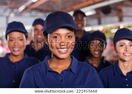 happy young african factory worker with colleagues - stock photo