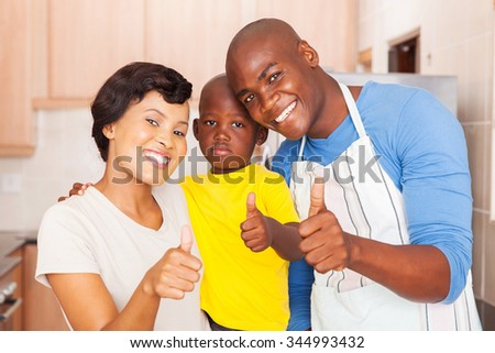 happy young african family giving thumbs up in kitchen - stock photo