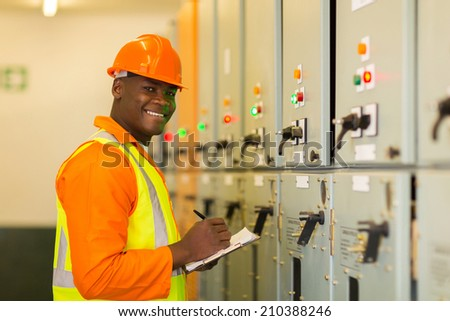 happy young African industrial technician taking machine readings - stock photo
