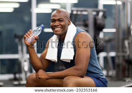 happy young african man drinking water after exercise - stock photo