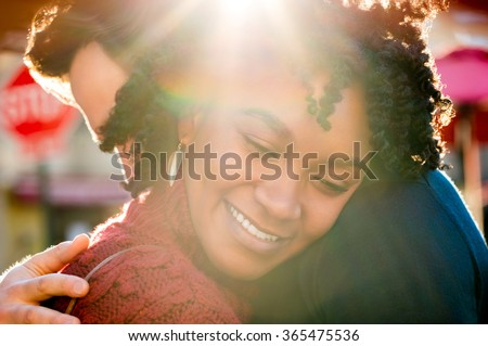 Happy young african woman hugging man in a bright sunny day. Close up face of young girl embracing her boyfriend and smiling with closed eyes. Romantic happy couple hugging outdoor. - stock photo