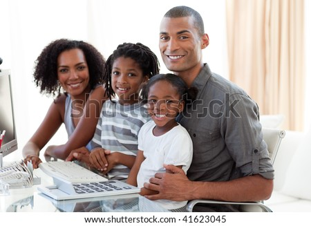 Happy young Afro-American family working with a computer at home - stock photo