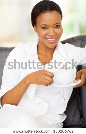 happy young afro american woman drinking coffee at home - stock photo