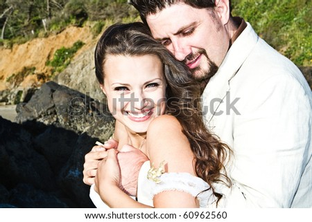 happy young and attractive wedding couple on the beach. - stock photo