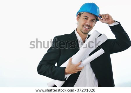 happy young architect portrait with helmet and blueprints indoor at new big bright apartment and construction site - stock photo