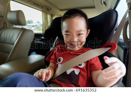 Happy young asian boy in safety carseat