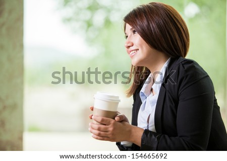Happy young Asian businesswoman looking up and thinking while drinking some coffee