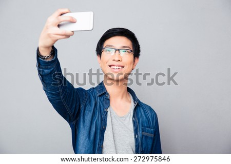 Happy young asian man making selfie photo on smartphone over gray background - stock photo