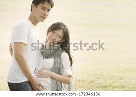 Happy young Asian pregnant couple outdoors. - stock photo