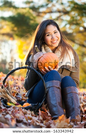 Happy young Asian woman holding a pumpkin in the fall in a pile of leaves at the park in autumn - stock photo