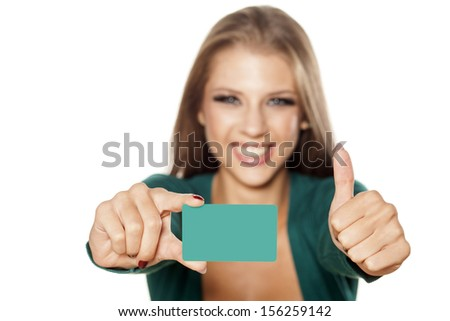 happy young attractive girl holding a credit card and showing thumbs up - stock photo