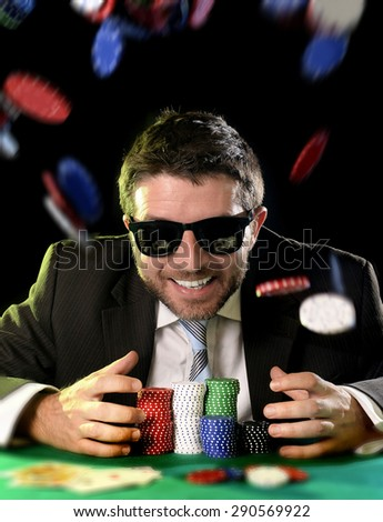 happy young attractive man grabbing and protecting poker chips with his hands after winning bet gambling at Casino with chips flying all around isolated on black background