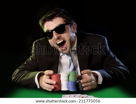 happy young attractive man grabbing poker chips after winning bet gambling on table with playing cards on green felt at Casino isolated on black background - stock photo