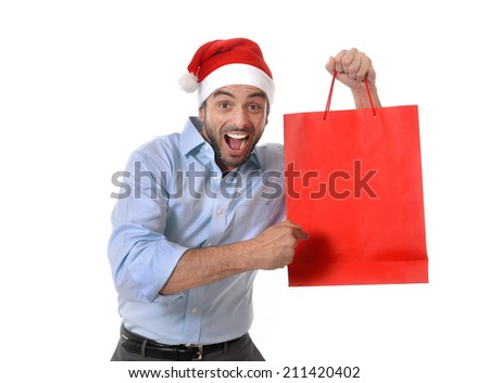 happy young attractive man wearing santa hat holding and pointing red shopping bag in christmas consumerism , sale, buying and xmas gifts and presents concept isolated on white background - stock photo