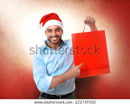 happy young attractive man wearing Santa hat holding and pointing red shopping bag in Christmas sales, consumerism,  buying xmas gifts and presents concept isolated on studio background - stock photo