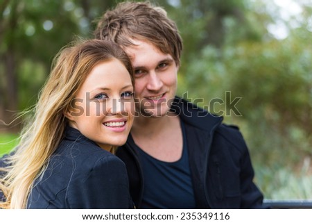 Happy young attractive woman smiling with his handsome boyfriend behind during a romantic time spent in a park - stock photo