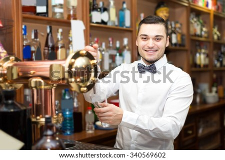 Happy young barman pouring beverages and smiling - stock photo