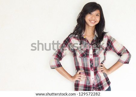 happy young beautiful asian girl posing and looking to the camera - stock photo