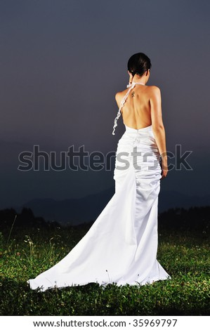 happy young beautiful bride after wedding ceremony event have fun on meadow in fashionable wedding dress - stock photo