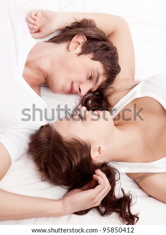 happy young beautiful couple in bed at home, top view - stock photo