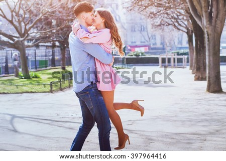 happy young beautiful couple kissing and smiling outdoors - stock photo