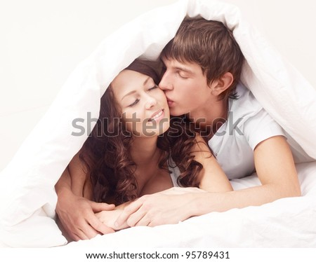 happy young beautiful couple under the blanket in bed at home - stock photo