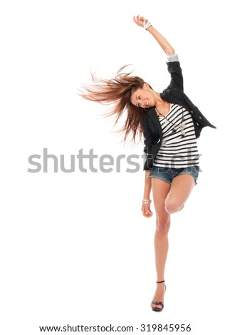 Happy young beautiful full body brunette woman dancing in casual cloth with windy hair isolated on a white background