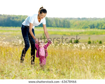 Happy young beautiful mather with smiling baby on nature - stock photo