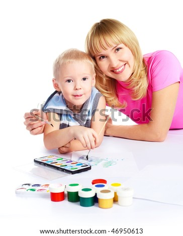 happy young beautiful mother and her little son painting with watercolor