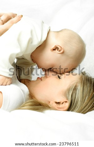 happy young beautiful mother lies on the white sofa with her baby - stock photo