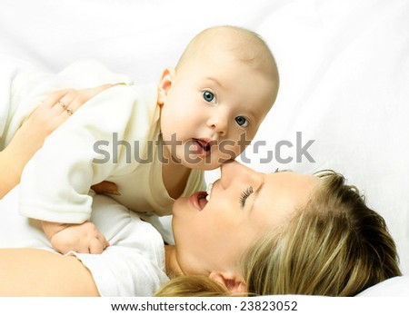 happy young beautiful mother on the white sofa with her baby - stock photo