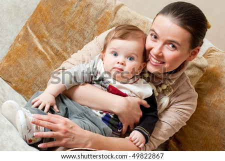 Happy young beautiful mother with her little son in home interior - stock photo