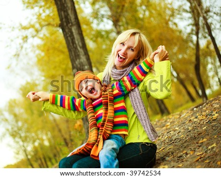 happy young beautiful mother with her little son in the park