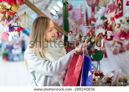 Happy young beautiful woman choosing Christmas decoration at market