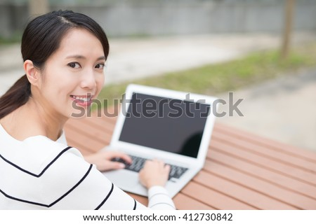Happy young beautiful woman relax sit and using laptop computer pc at park, asian beauty - stock photo