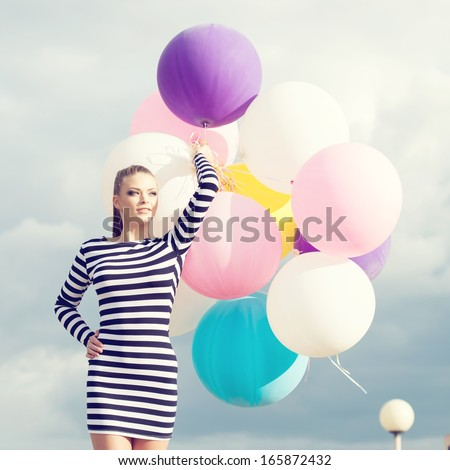 Happy young beautiful woman standing  with colorful latex balloons. Outdoors, lifestyle - stock photo