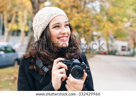 Happy young beautiful woman with an analog camera capturing autumn in the city - stock photo