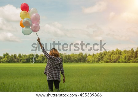 Happy young beautiful woman with balloons in the grass field enjoy with fresh air. - stock photo