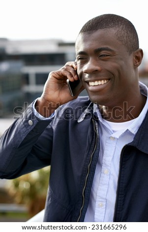 happy young black african man with cell phone having conversation on mobile - stock photo