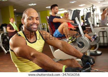 Happy young black man training in gym in rowing machine, smiling, looking at camera. - stock photo