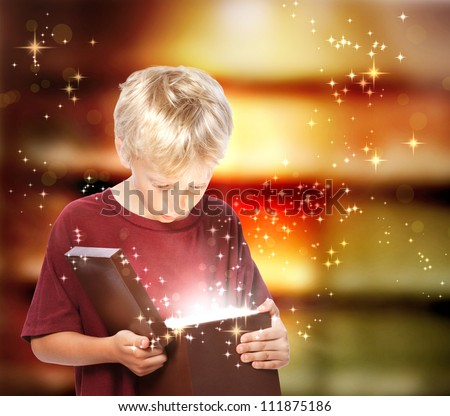 Happy Young Blond Boy Opening a Gift Box - stock photo