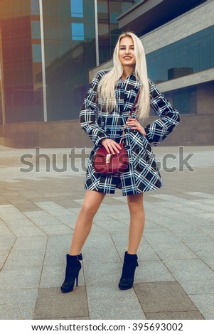 Happy young blond girl smiling on the camera outdoors. fashion model posing outdoors. fashionable and glamour concept.