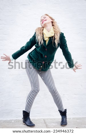 Happy young blond hipster woman wearing stripped trousers funny posing over white brick wall copy space background - stock photo
