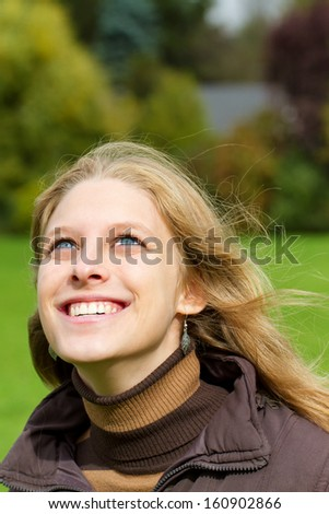 Happy young blond woman looking the sky.