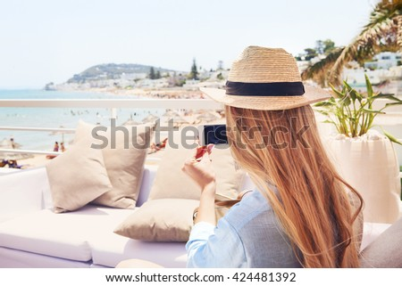 Happy young blond woman taking smartphone photo with smart phone  of a beach in Gammarth Tunis, Tunisia on outdoor patio sofa furniture