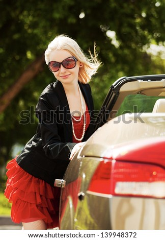 Happy young blond woman with a new convertible car