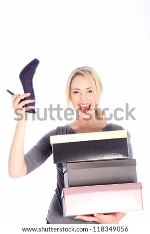 Happy young blonde woman holding three shoe boxes with high heel in right hand on white background - stock photo