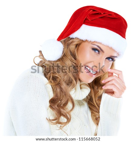 Happy young blonde woman smiling with a red Christmas hat on - stock photo